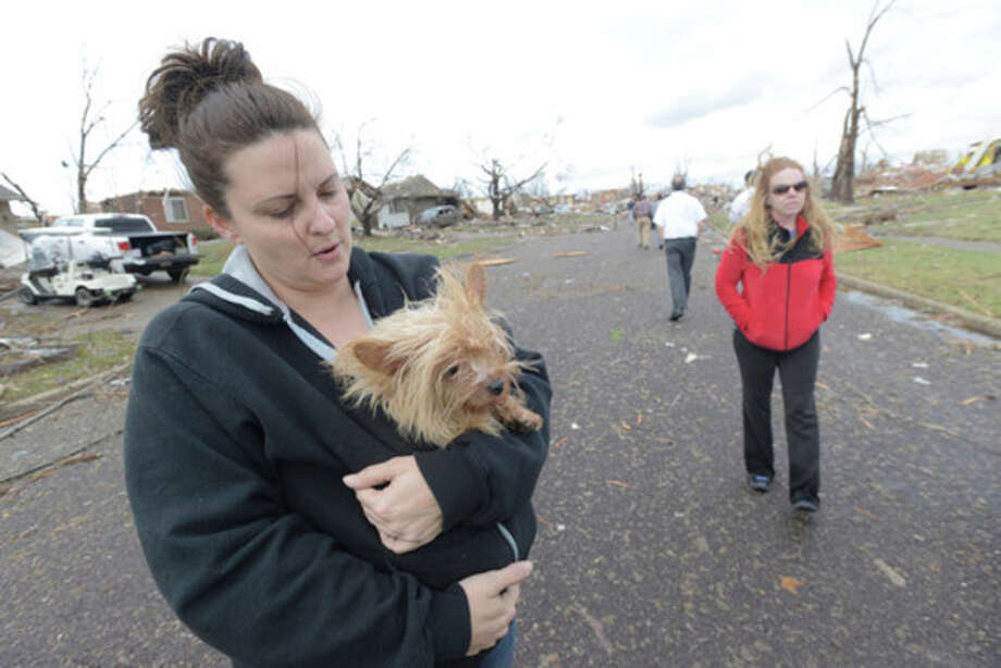 Aimee Royer holds a dog she rescued from debris after a Sunday morning tornado sliced through a subdivision on the North side of Washington, Ill., Sunday, Nov. 17, 2013. Royer and her friend, Kendra Gray, at right, said their home was spared. Several homes are cleared down to the foundation. Intense thunderstorms and tornadoes swept across the Midwest, causing extensive damage in several central Illinois communities while sending people to their basements for shelter. (AP Photo/The Pantagraph, Steve Smedley) / The Pantagraph