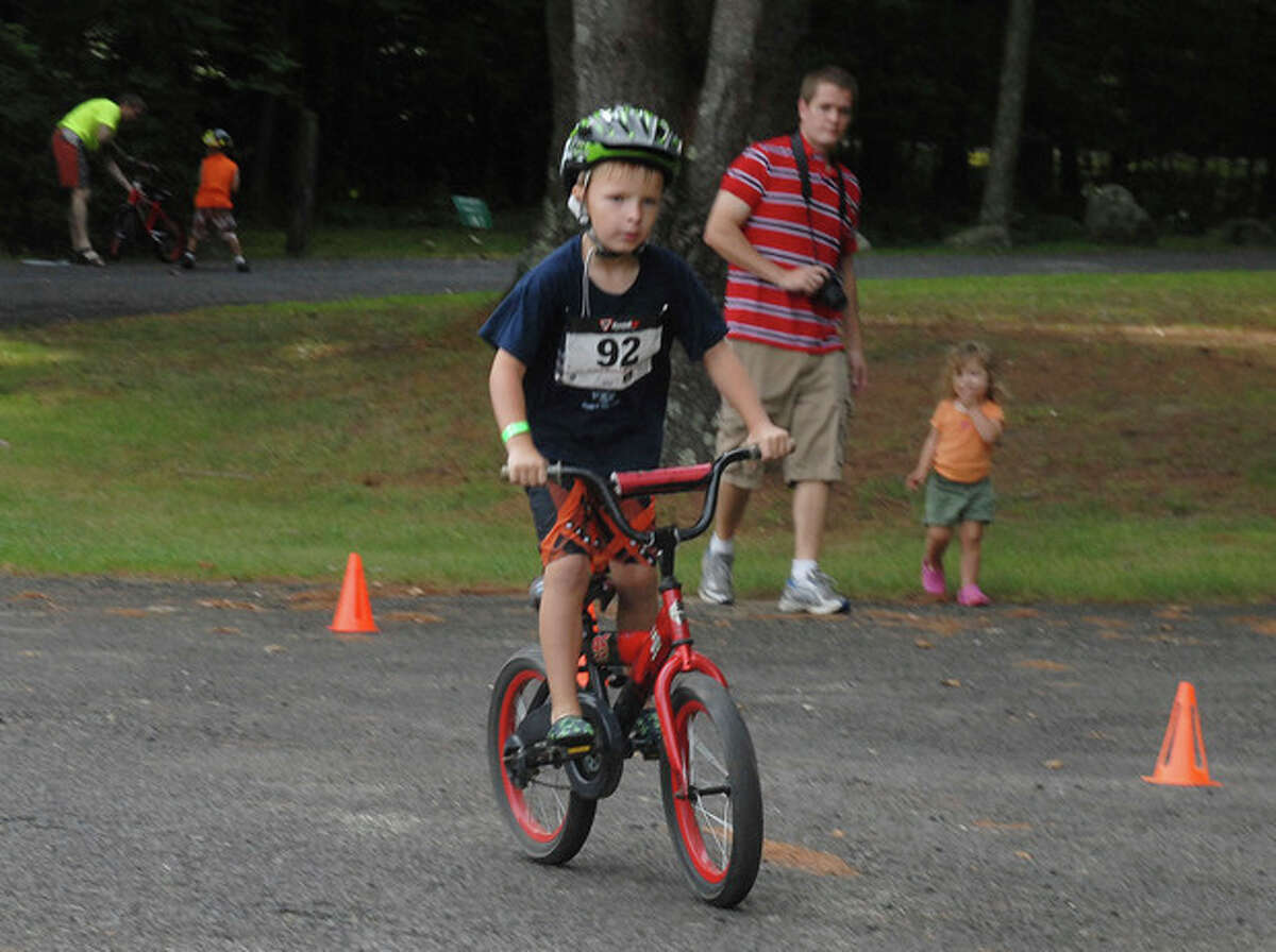 In this 2012 file photo provided by the Kowalski family, Chase Kowalski bikes during the 2012 Kids Who Tri Succeed Triathlon in Mansfield, Conn. Chase Kowalski loved to race, whether it was running, swimming or riding his bike. The 7-year-old, one of 26 people killed last Dec. 14 inside the Sandy Hook Elementary school, ran competitively for the first time when he was just 2½ years old. His parents decided to honor Chase?'s memory by a starting a foundation, raising money for children?'s fitness projects, family wellness and preschool education scholarships. (AP Photo/Kowalski family)