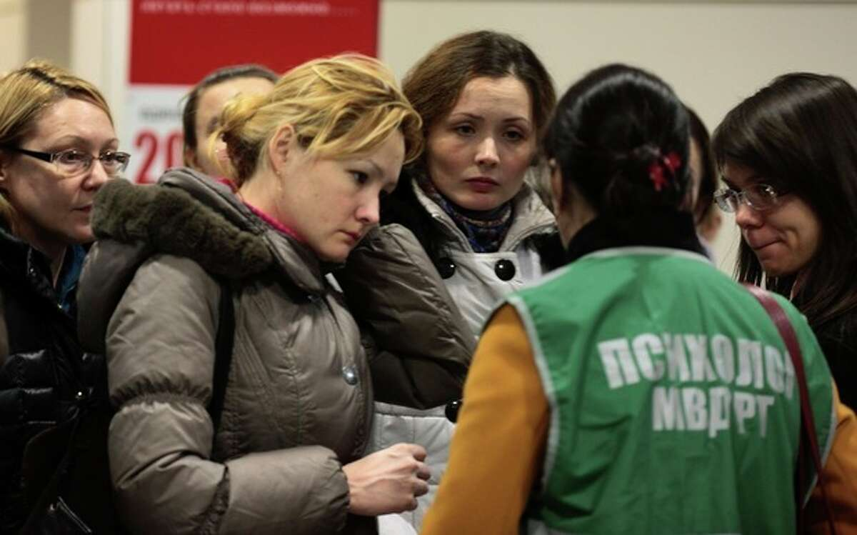 A psychologist at the airport speaks to relatives and friends of those who were aboard the Russian passenger airliner, Boeing 737, crashed in Kazan, about 720 kilometers (450 miles) east of Moscow, Sunday, Nov. 17, 2013. A Russian passenger airliner crashed Sunday night while trying to land at the airport in the city of Kazan, killing all people aboard, officials said. The Boeing 737 belonging to Tatarstan Airlines crashed an hour after taking off from Moscow. There were no immediate indications of the cause. (AP Photo/Nikolai Alexandrov)
