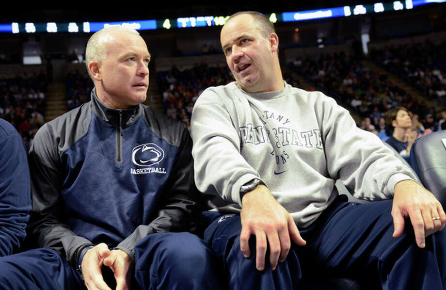 Penn State head men's basketball coach Patrick Chambers, left, and Penn State head football coach Bill O'Brien talk during a timeout of the Penn State against Connecticut women's NCAA college basketball game on Sunday, Nov. 17, 2013, in State College, Pa. Connecticut defeated Penn State 71 - 52. (AP Photo/John Beale) / FR157268 AP