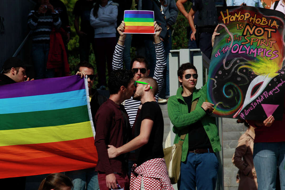 FILE - In this Saturday, Oct. 5, 2013 file photo, Gay activists kiss during a protest at the steps of the Acropolis' museum during an event ahead of the handover ceremony of the Olympic Flame, in Athens. A few dozen gay activists peacefully protested at Russia?'s restrictive laws against ?