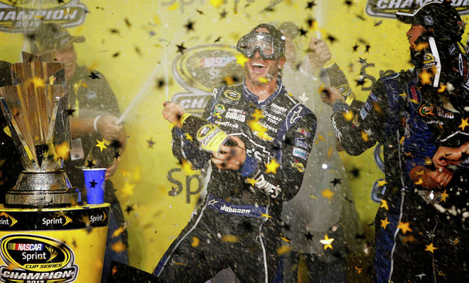 Jimmie Johnson celebrates after winning his sixth NASCAR Sprint Cup Series auto race title in eight years in Homestead, Fla., Sunday, Nov. 17, 2013. (AP Photo/Terry Renna) / FR60642 AP