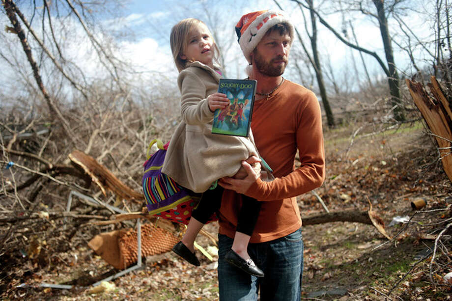East Peoria resident Billy Vestal evacuates with his daughter, Lillian Vestal, 3, after a tornado damaged the area near Chestnut Road in East Peoria, Il.,Sunday, Nov. 17, 2013. Intense thunderstorms and tornadoes swept across the Midwest on Sunday, causing extensive damage in several central Illinois communities while sending people to their basements for shelter (AP Photo/Journal Star, Justin Wan) MANDATORY CREDIT / Journal Star