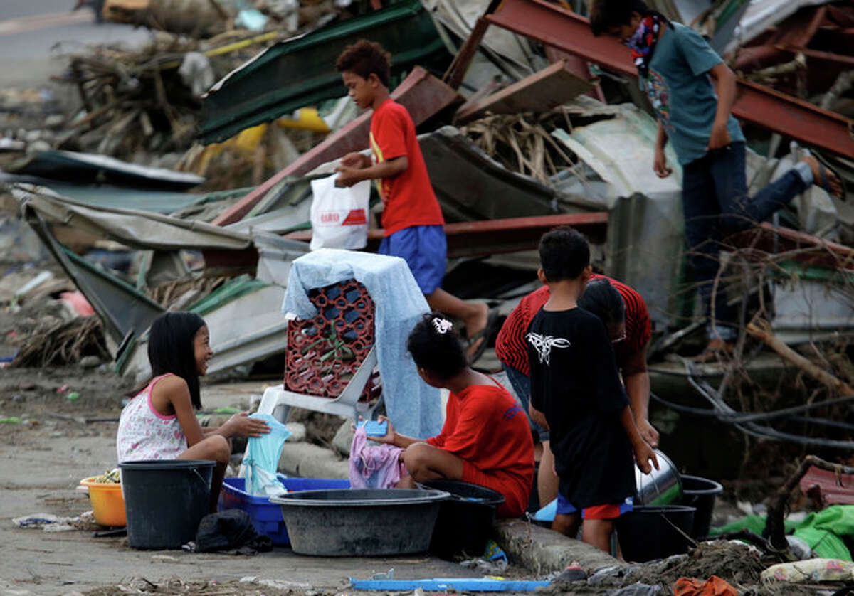 Typhoon survivors do their laundry along a roadside, Sunday Nov. 17, 2013 at typhoon-ravaged Tacloban city, Leyte province in central Philippines. Typhoon Haiyan, one of the most powerful typhoons ever recorded, slammed into central Philippine provinces on Nov. 8, leaving a wide swath of destruction and thousands of people dead. (AP Photo/Bullit Marquez)