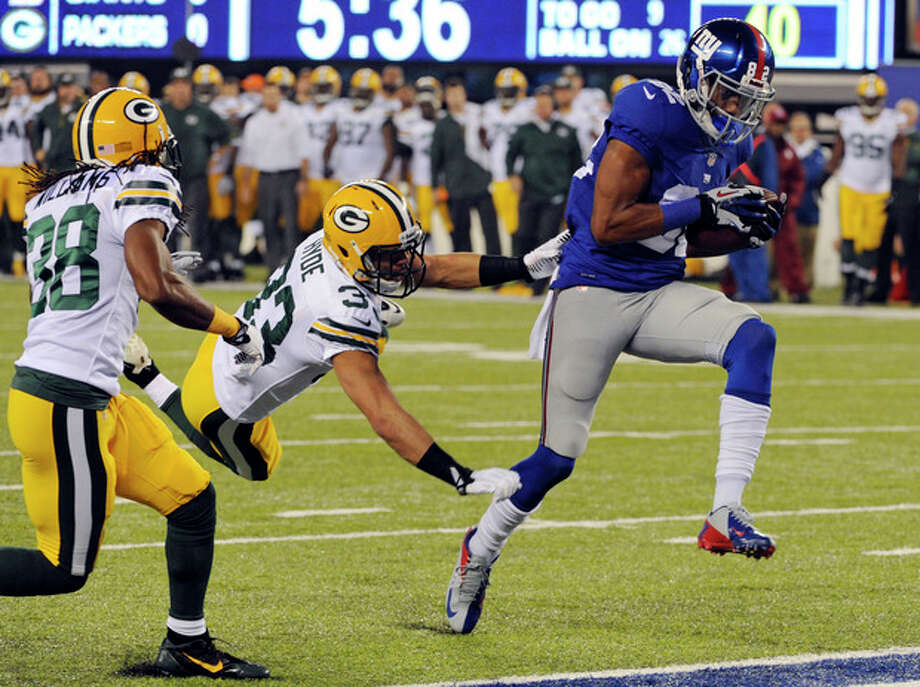 New York Giants wide receiver Rueben Randle breaks away from Green Bay Packers cornerback Micah Hyde (33) and Tramon Williams (38) for a touchdown during the first half of an NFL football game Sunday, Nov. 17, 2013, in East Rutherford, N.J. (AP Photo/Bill Kostroun) / FR51951 AP