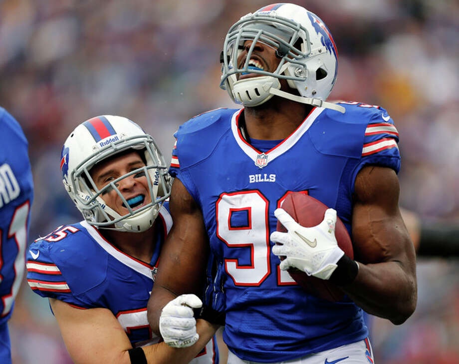 Buffalo Bills outside linebacker Manny Lawson, right, celebrates a fumble recover with teammate Jim Leonhard during the first half of an NFL football game against the New York Jets on Sunday, Nov. 17, 2013, in Orchard Park, N.Y. (AP Photo/Gary Wiepert) / FR170498 AP