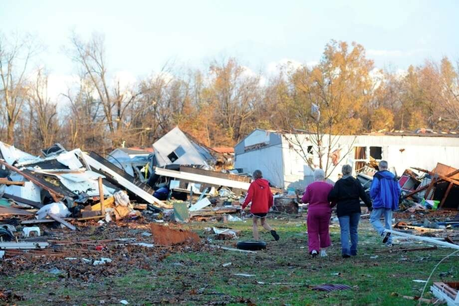 An elderly woman is escorted through tornado debris in Brookport, Ill., Sunday, Nov. 17, 2013. The small far southern Illinois town was hit by severe weather. (AP Photo/Stephen Lance Dennee) / FR170568 AP