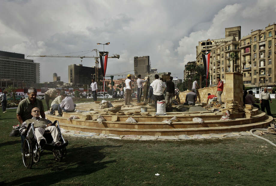 In this Sunday, Nov. 17, 2013 photo, Egyptian municipality laborers work on a memorial base two days before the commemoration of deadly clashes with security forces in 2011, in Tahrir Square, Cairo. Egypt's government wants the memorial to commemorate those killed in protests over two years of unrest in the country, but some say the memorial is just a means to make it appear there's political stability in the Arab world's most populous nation. (AP Photo/Nariman El-Mofty) / AP