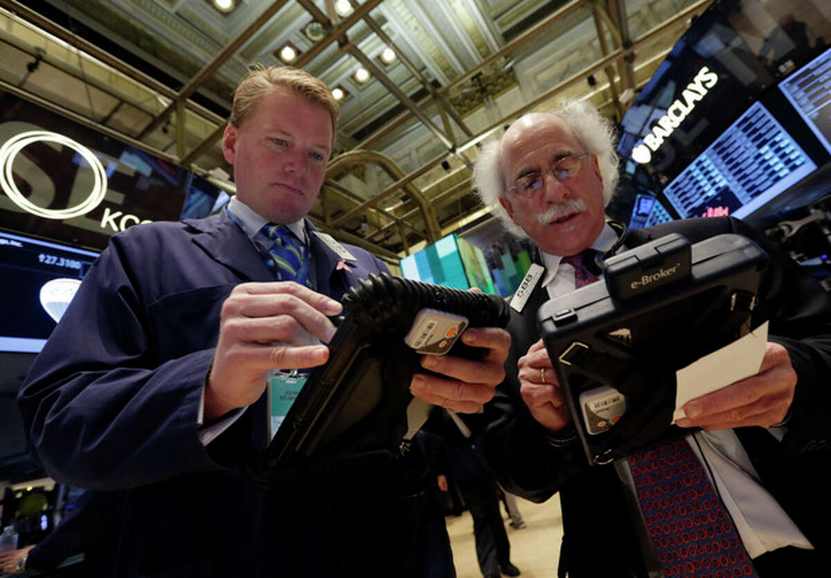 FILE - In this Tuesday, Nov. 12, 2013, file photo, traders John Bowers, left, and Peter Tuchman work on the floor of the New York Stock Exchange. (AP Photo/Richard Drew, File)