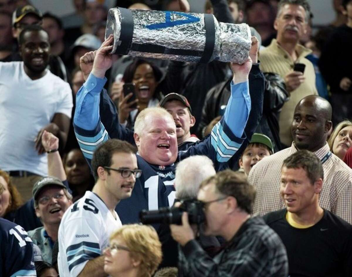 Toronto Mayor Rob Ford holds up a replica Grey Cup as he attends the Toronto Argonauts and Hamilton Tiger-Cats CFL Eastern Conference final football game in Toronto on Sunday, Nov. 17, 2013. (AP Photo/The Canadian Press, Nathan Denette)