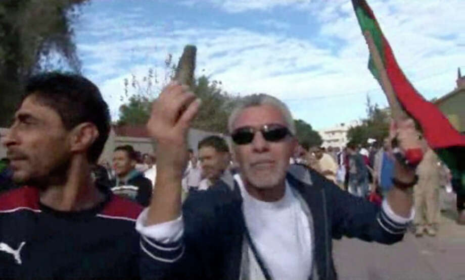 This image made from video shows a protester holding up spent ammunition in Tripoli, Libya after militiamen attacked peaceful protesters demanding the disbanding of the country's rampant armed groups on Friday, Nov. 15, 2013, killing tens of people as they opened fire on the march with heavy machine guns and rocket-propelled grenades. (AP Photo via AP video) / APTN