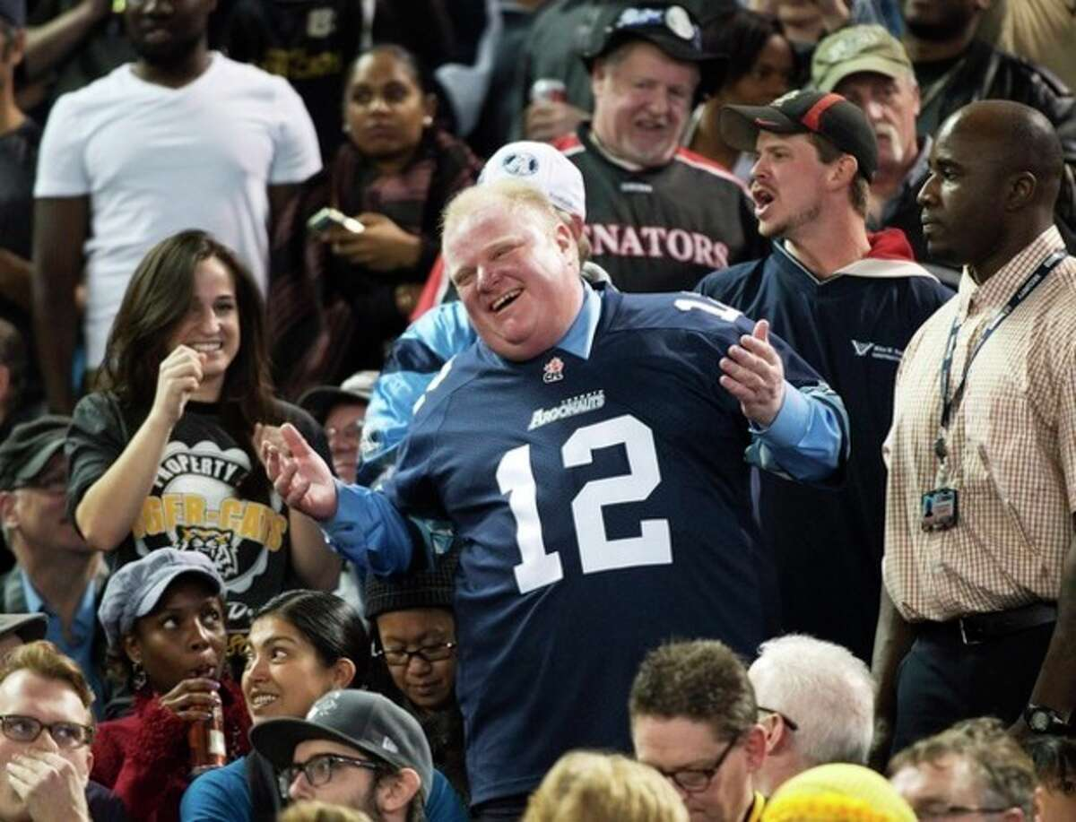Toronto Mayor Rob Ford laughs with fans as he attends the Toronto Argonauts and Hamilton Tiger-Cats CFL Eastern Conference final football game in Toronto on Sunday, Nov. 17, 2013. Ford showed up at Sunday's Canadian Football League playoff game, despite a request by the league's commissioner that he stay away. (AP Photo/The Canadian Press, Nathan Denette)