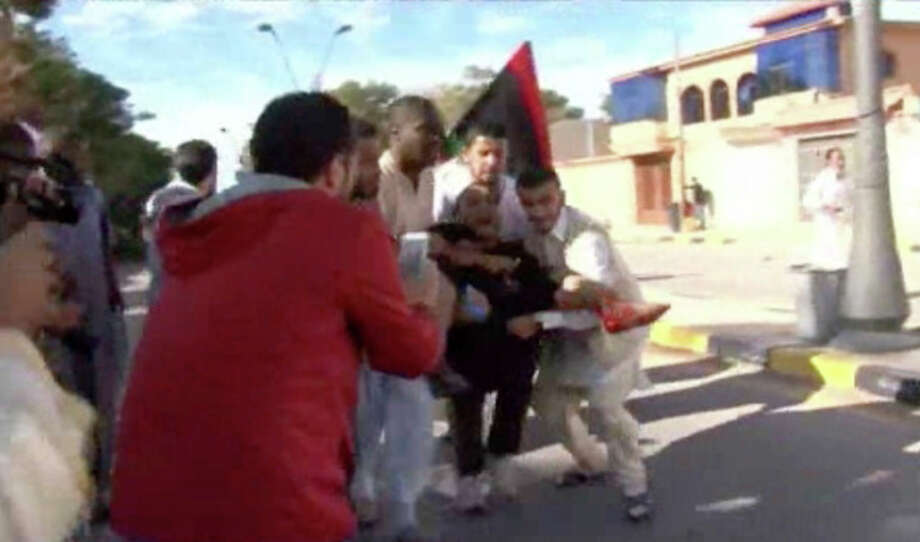 This image made from video shows an injured protester being carried away from the scene in Tripoli, Libya after militiamen attacked peaceful protesters demanding the disbanding of the country's rampant armed groups on Friday, Nov. 15, 2013, killing tens of people as they opened fire on the march with heavy machine guns and rocket-propelled grenades. (AP Photo via AP video) / APTN