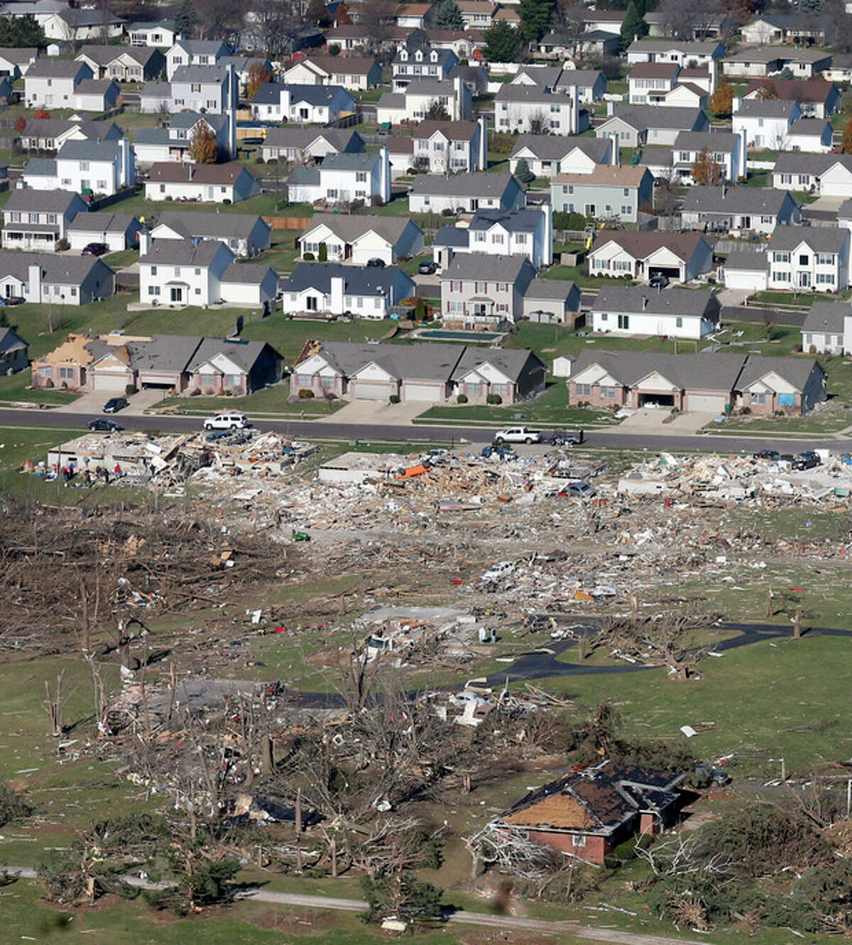This aerial view on Monday, Nov. 18, 2013, shows untouched homes and homes destroyed by a tornado that hit the western Illinois town of Washington on Sunday. It was one of the worst-hit areas after intense storms and tornadoes swept through Illinois. The National Weather Service says the tornado that hit Washington had a preliminary rating of EF-4, meaning wind speeds of 170 mph to 190 mph. (AP Photo/Charles Rex Arbogast)