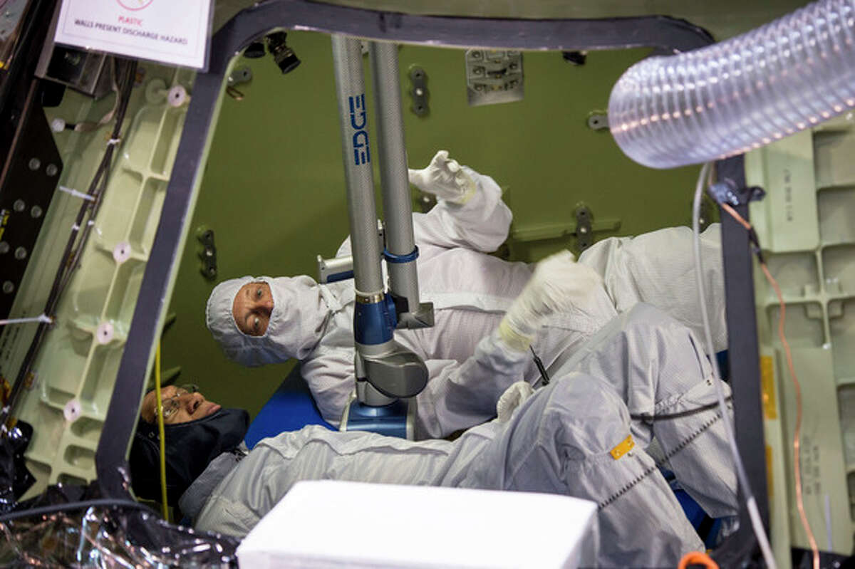 This photo provided by NASA shows NASA administrator Charles Bolden, foreground, and Scott McDade with Lockheed Martin, inspecting the Orion Multipurpose Crew Vehicle, which is being processed for its first test flight, Sunday, Nov. 17, 2013, at the Kennedy Space Center's Operation and Checkout Facility in Cape Canaveral, Florida. The spacecraft that will one day carry astronauts to study an asteroid and eventually on to Mars is being prepared for its maiden flight by engineers from NASA and Lockheed Martin. Orion's first exploration flight test is scheduled for late 2014. The Administrator is at the Kennedy Space Center for the launch of MAVEN to Mars, targeted for liftoff Monday, Nov. 18, at 1:28 p.m. EST. (AP Photo/NASA, Bill Ingalls)