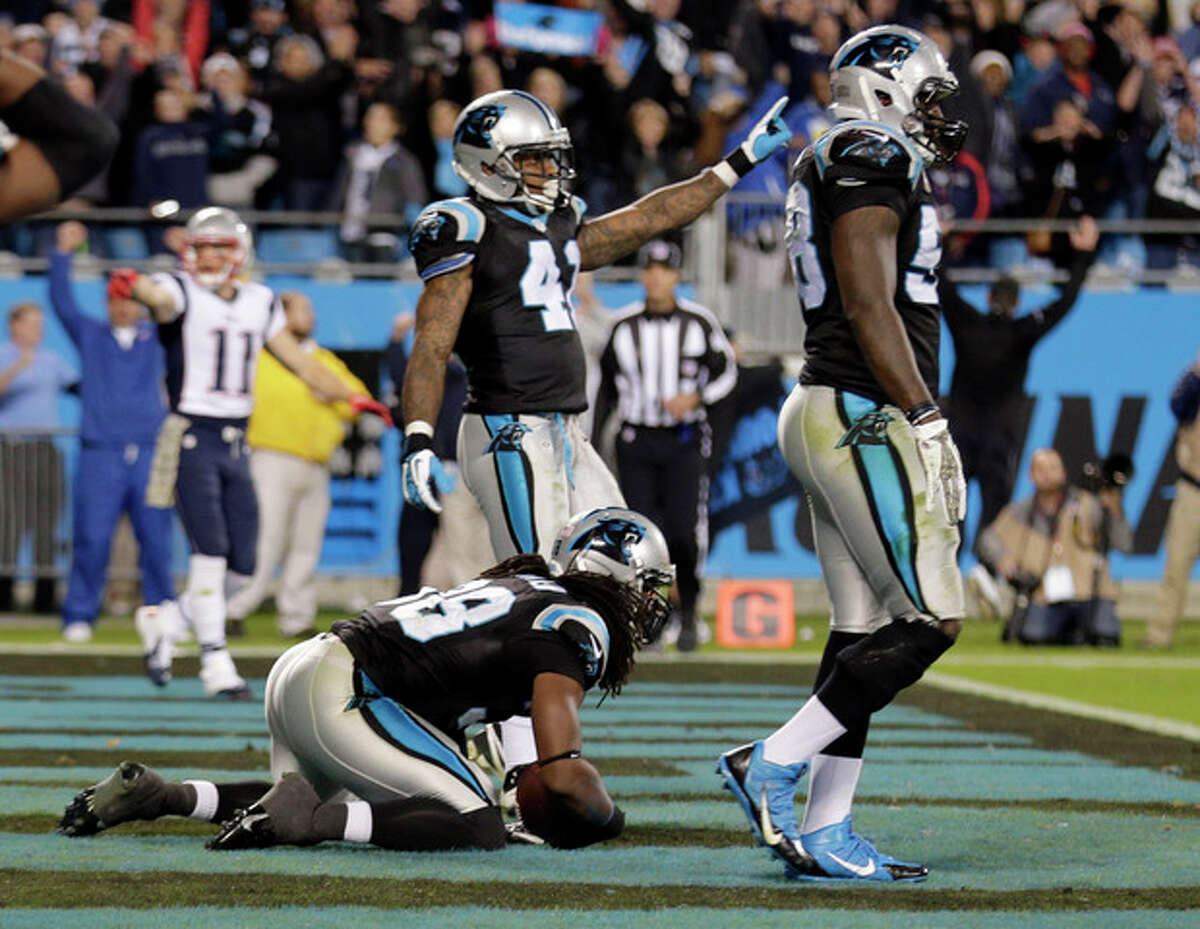 Carolina Panthers' Robert Lester, center, intercepts a New England Patriots pass on the final play of an NFL football game in Charlotte, N.C., Monday, Nov. 18, 2013. The Panthers won 24-20. (AP Photo/Chuck Burton)