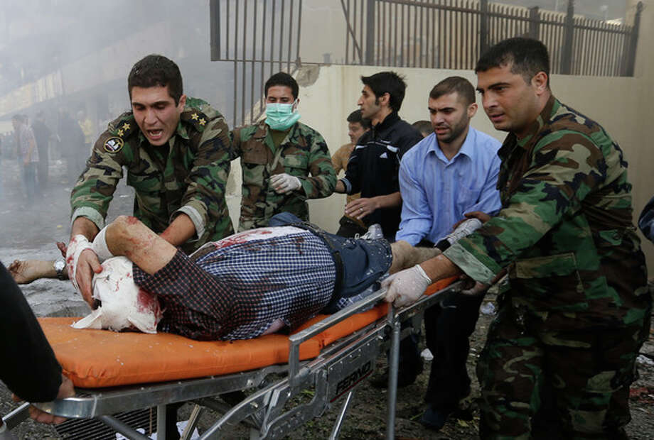 Lebanese army soldiers, help an injured man at the scene where two explosions have struck near the Iranian Embassy killing several, in Beirut, Lebanon, Tuesday, Nov. 19, 2013. The blasts in south Beirut's neighborhood of Janah also caused extensive damage on the nearby buildings and the Iranian mission. The area is a stronghold of the militant Hezbollah group, which is a main ally of Syrian President Bashar Assad in the civil war next door. It's not clear if the blasts are related to Syria's civil war. (AP Photo/Hussein Malla) / AP