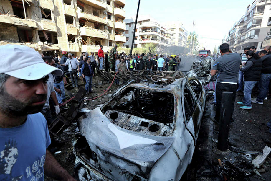 Lebanese people gather at the scene where two explosions have struck near the Iranian Embassy killing many, in Beirut, Lebanon, Tuesday, Nov. 19, 2013. The blasts in south Beirut's neighborhood of Janah also caused extensive damage on the nearby buildings and the Iranian mission. The area is a stronghold of the militant Hezbollah group, which is a main ally of Syrian President Bashar Assad in the civil war next door. It's not clear if the blasts are related to Syria's civil war. (AP Photo/Bilal Hussein) / AP