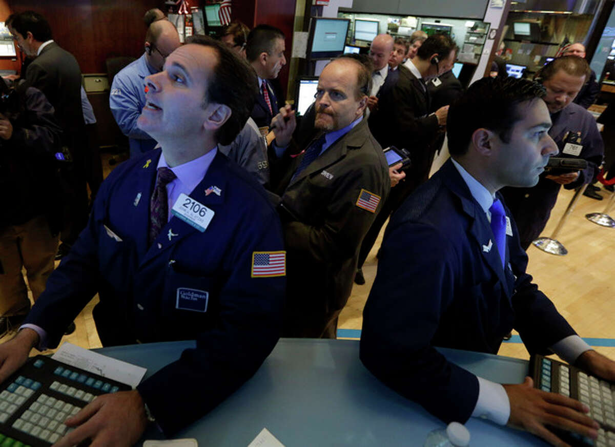 Specialists John Alatzas, left, and William Geier, right, work at their posts on the floor of the New York Stock Exchange, Tuesday, Nov. 19, 2013. Stocks are lower in early trading on Wall Street as traders pick over some disappointing corporate earnings. (AP Photo/Richard Drew)