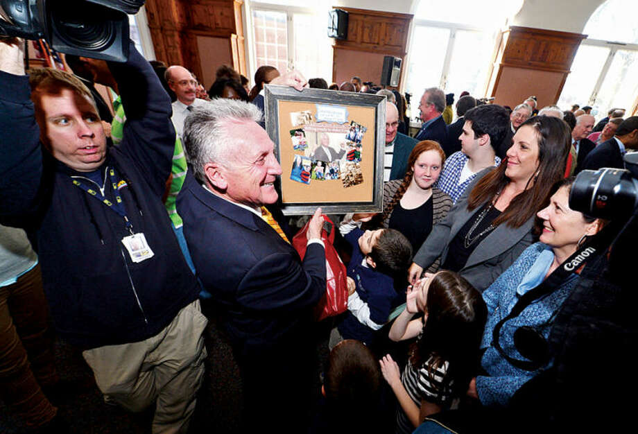 Hour photo / Erik Trautmann Harry Rilling displays a collage made for him by his family after being sworn in as mayor of Norwalk Tuesday afternoon in the Community Room at City Hall.