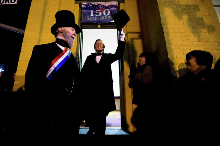 President Abraham Lincoln, portrayed by presenter Robert Costello, center, accompanied by David Wills, who is portrayed by presenter Joe Mieczkowski, tips his hat Monday, Nov. 18, 2013, at the Gettysburg Train Station in Gettysburg, Pa. Tuesday, Nov. 19, marks the 150th anniversary of Lincoln's short speech that has gone on to symbolize his presidency and explain the sacrifices made by Union and Confederate forces during the U.S. Civil War. (AP Photo/Matt Rourke) / AP