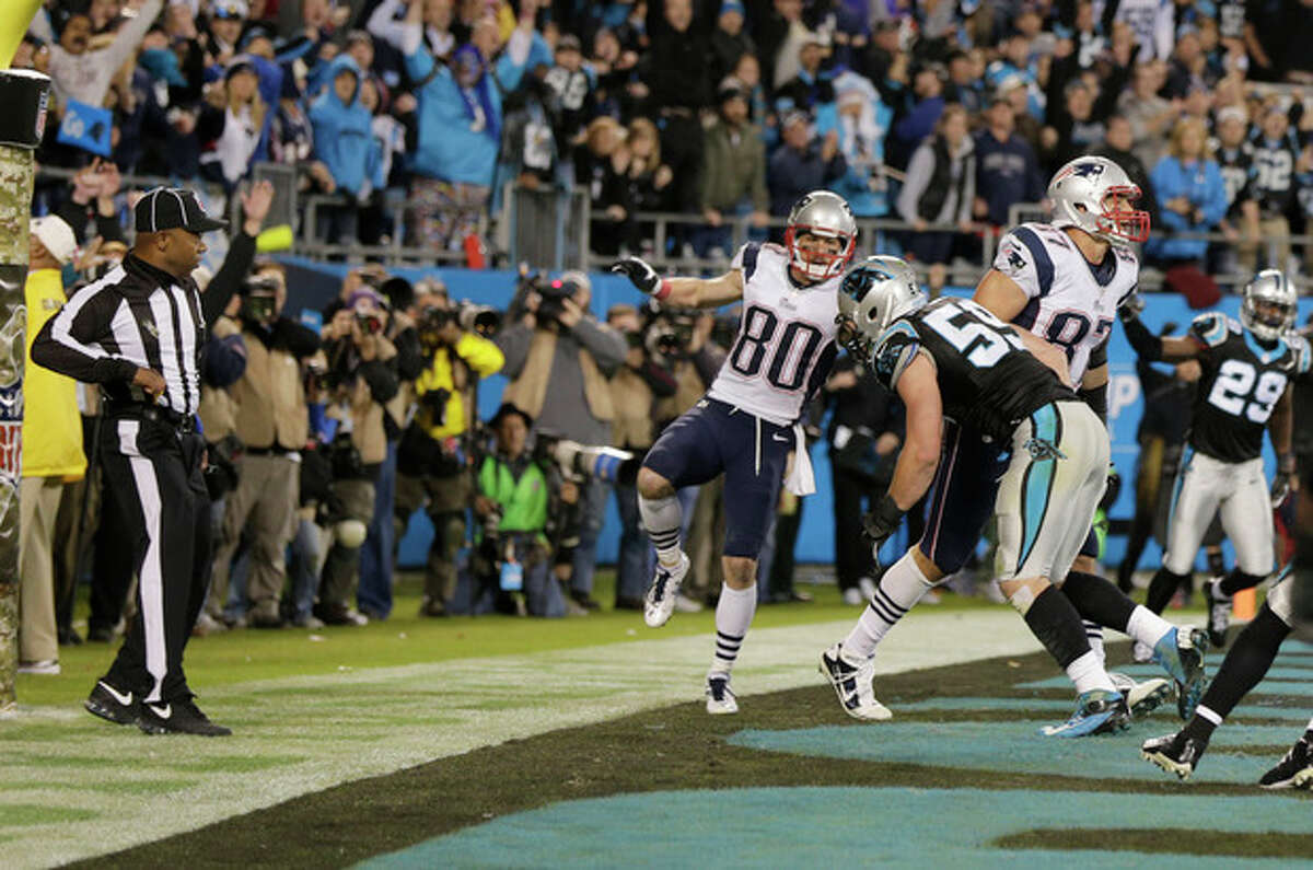 An official, left, reaches for his flag as Carolina Panthers' Luke Kuechly (59) hits New England Patriots' Rob Gronkowski (87) in the end zone on the last play of an NFL football game in Charlotte, N.C., Monday, Nov. 18, 2013. They ruled no plenty on the play. (AP Photo/Chuck Burton)