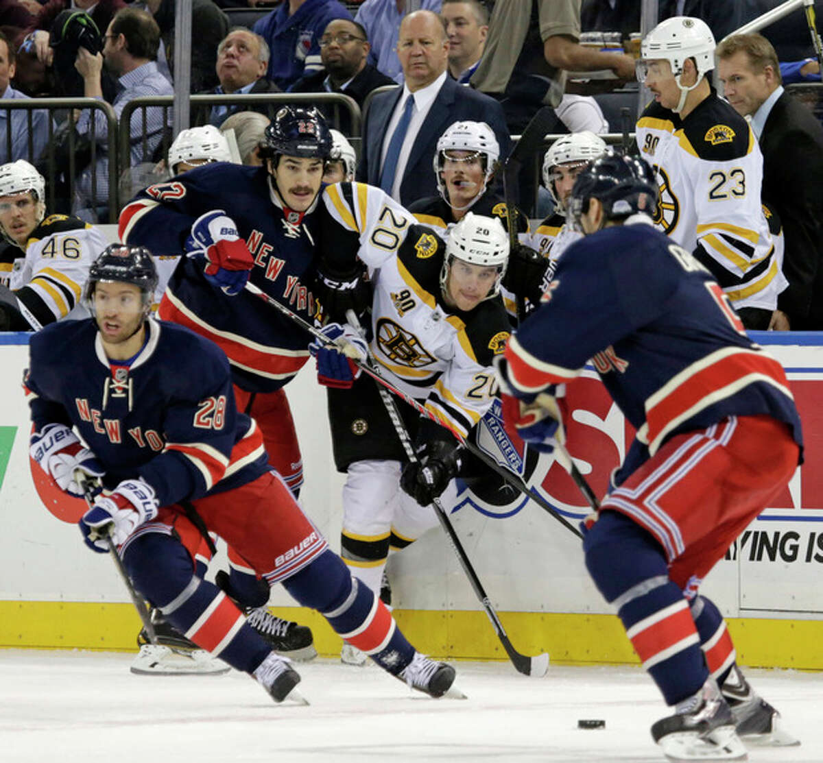 New York Rangers center Brian Boyle (22) passes to New York Rangers defenseman Dan Girardi (5), right foreground, with Boston Bruins left wing Daniel Paille (20) defending in the first period of their NHL hockey game at Madison Square Garden in New York, Tuesday, Nov. 19, 2013. (AP Photo/Kathy Willens)