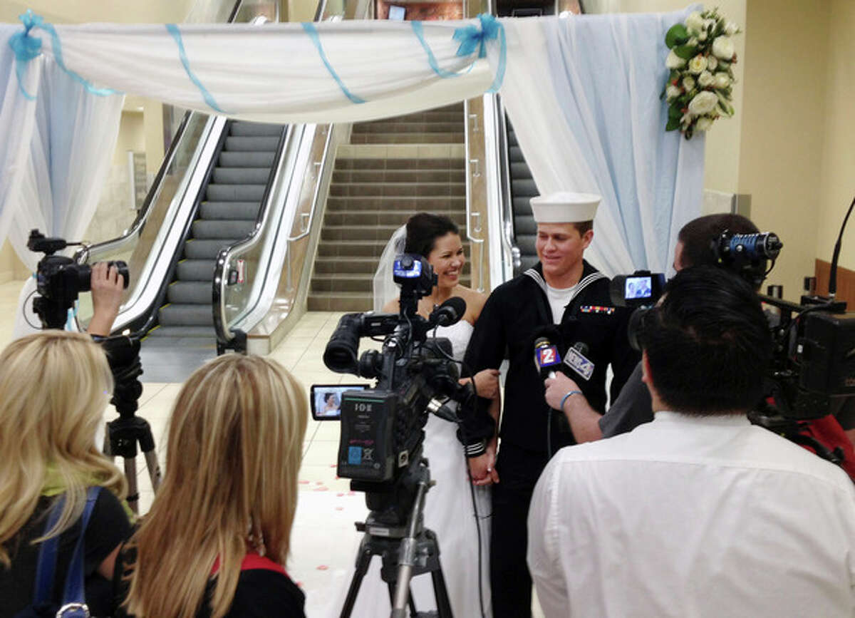 In this photo courtesy of Heidi Jared, taken on Tuesday Nov. 19, 2013, U.S. Navy seaman Dylan Ruffer and his fiancee, Madison Meinhardt, both from Chester, Calif., talk to news reporters after getting married in front of the arrivals escalators at the Reno-Tahoe International Airport in Reno, Nev. Ruffer married his high school sweetheart just moments after returning from an 11-month deployment off the coast of war-torn Syria. More than 200 invited guests, passengers and others looked on. (AP Photo/Courtesy Heidi Jared)