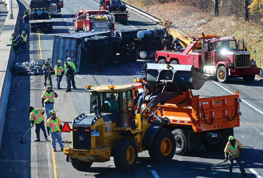Hour photo / Erik Trautmann A tractor trailer carrying scrap metal turns over on I-95 near exit 14 closing the southbound side of highway for hours Wednesday afternoon.