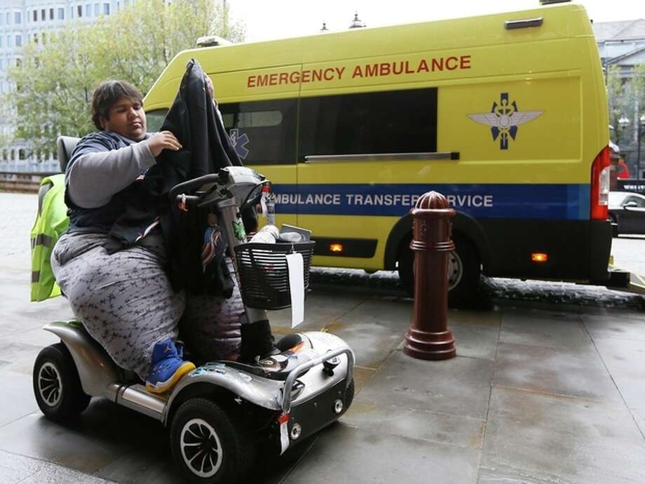 Kevin Chenais puts on his jacket as he sits in his mobility scooter in front of an ambulance at St Pancras in London, Wednesday, Nov. 20, 2013. Kevin, who suffers from a medical condition will travel by ambulance and ferry back to France. Eurostar says it refused travel on its trains to the Frenchman who was earlier stranded in the United States because he was deemed too fat to fly home. The service that connects England to France and Belgium declined to allow Kevin Chenais on board because of safety rules governing travel through the Channel Tunnel. Eurostar says provisions require all passengers to have the ability to be safely evacuated and Chenais' immobility makes this impossible. (AP Photo/Kirsty Wigglesworth) / AP