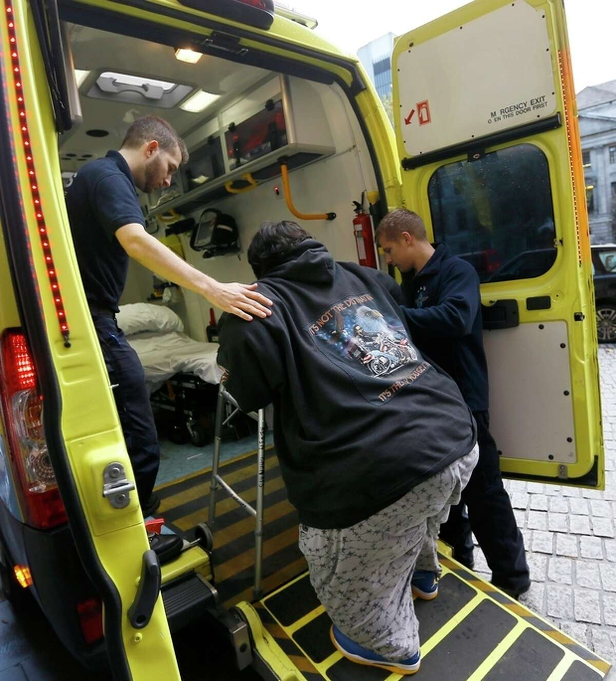 Kevin Chenais, centre, is assisted by ambulance staff onto an ambulance at St Pancras in London, Wednesday, Nov. 20, 2013. Kevin, who suffers from a medical condition will travel by ambulance and ferry back to France. Eurostar says it refused travel on its trains to the Frenchman who was earlier stranded in the United States because he was deemed too fat to fly home. The service that connects England to France and Belgium declined to allow Kevin Chenais on board because of safety rules governing travel through the Channel Tunnel. Eurostar says provisions require all passengers to have the ability to be safely evacuated and Chenais' immobility makes this impossible. (AP Photo/Kirsty Wigglesworth)