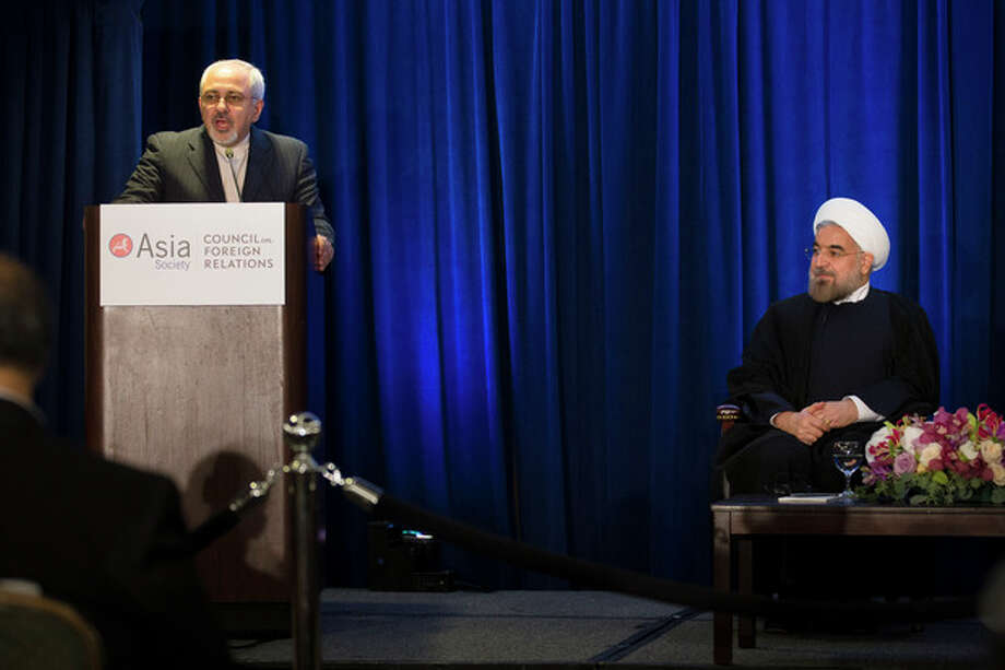FILE - In this Thursday, Sept. 26, 2013, file photo, Iranian President Hassan Rouhani, right, listens as Iranian Foreign Minister Mohammad Javad Zarif, left, updates the audience on the results of his bilateral meeting with U.S. Secretary of State John Kerry, during a address and discussion hosted by the Asia Society and the Council on Foreign Relations at the Hilton Hotel in New York. Iran has suddenly gone public with a significant concession just days ahead of a new round of talks with six world powers that begin Wednesday, Nov. 20, 2013 in Geneva. It still insists that it has a right to enrich uranium, but it now says that the six no longer need to publicly acknowledge its claim, opening a way to sidestep the dispute and focus on more practical steps both sides can agree on. (AP Photo/John Minchillo, File) / FR170537 AP