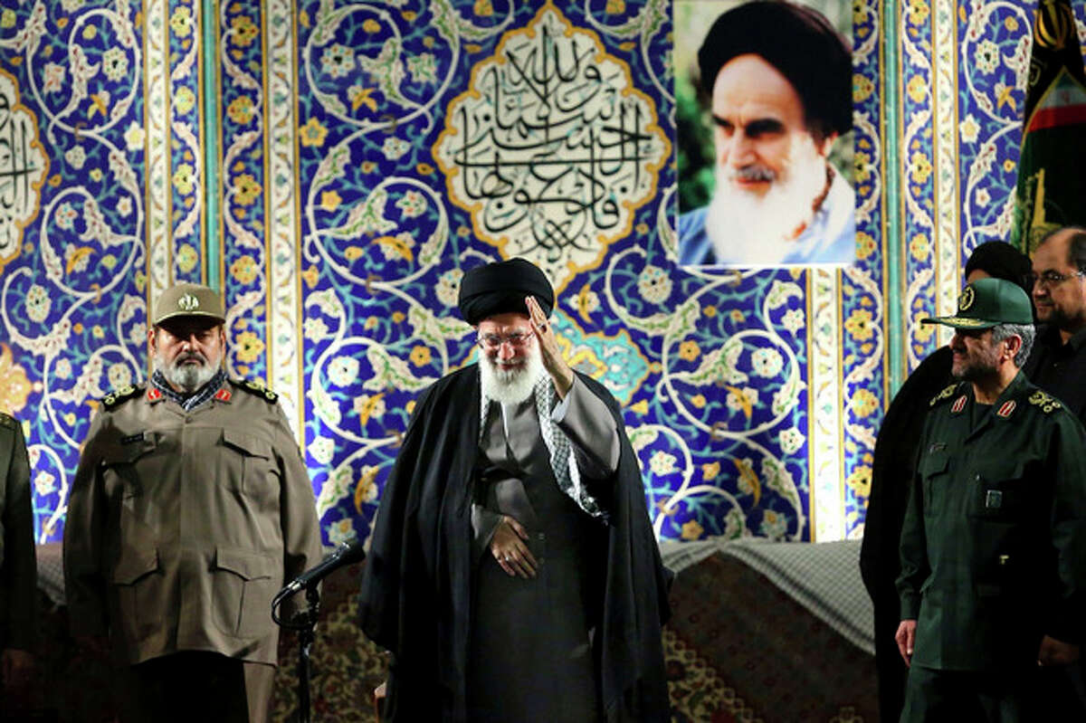 In this photo released by an official website of the Iranian supreme leader's office on Wednesday, Nov. 20, 2013, Iran's Supreme Leader Ayatollah Ali Khamenei waves to members of the paramilitary Basij force at the Imam Khomeini Grand Mosque in Tehran, Iran. Khamenei says pressure from economic sanctions will never force the country into unwelcome concessions as nuclear negotiators resumed talks with world powers. Khamenei also blasted U.S. government policies, including threats of military action, but said Iran has