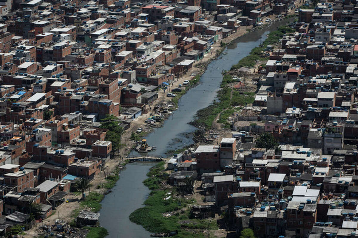 A polluted channel runs through the Rio das Pedras shantytown in Rio de Janeiro, Brazil, Tuesday, Nov. 19, 2013. It?'s not clear what consequences there might be if Rio doesn?'t clean up its waterways, but this isn?'t the first time the Olympics have faced steep environmental challenges. (AP Photo/Felipe Dana)