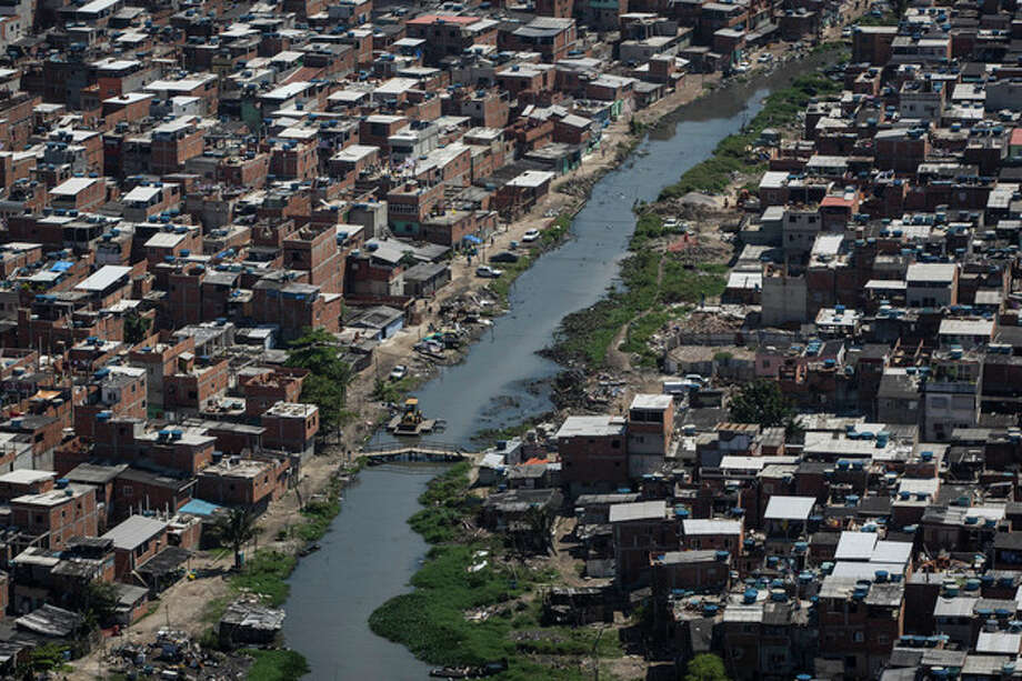 A polluted channel runs through the Rio das Pedras shantytown in Rio de Janeiro, Brazil, Tuesday, Nov. 19, 2013. It's not clear what consequences there might be if Rio doesn't clean up its waterways, but this isn't the first time the Olympics have faced steep environmental challenges. (AP Photo/Felipe Dana) / AP
