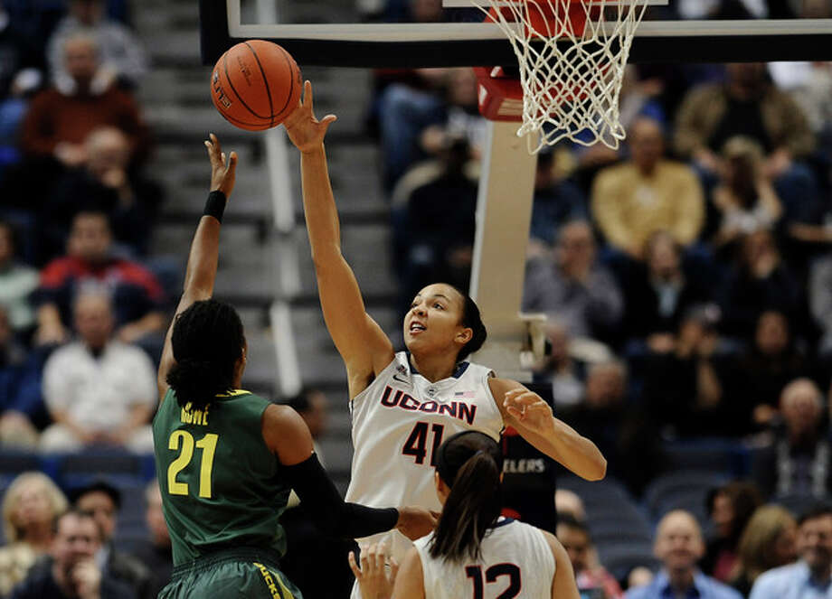 Connecticut's Kiah Stokes, right, blocks a shot attempt by Oregon's Chrishae Rowe, left, during the first half of an NCAA college basketball game, Wednesday, Nov. 20, 2013, in Hartford, Conn. (AP Photo/Jessica Hill) / FR125654 AP