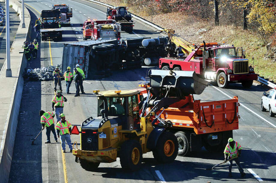 Hour photo / Erik TrautmannA tractor trailer carrying scrap metal turns over on I-95 near exit 14 closing the southbound side of the highway for hours Wednesday afternoon. / (C)2013, The Hour Newspapers, all rights reserved