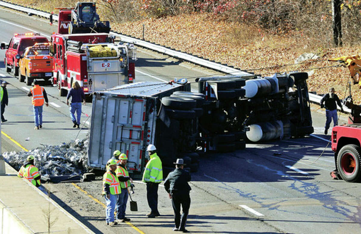 Hour photo / Erik Trautmann A tractor trailer carrying scrap metal turns over on I-95 near exit 14 closing the southbound side of the highway for hours Wednesday afternoon.