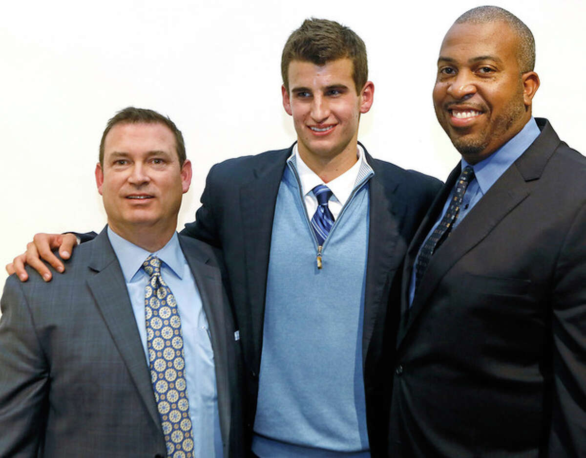 Loyola High School senior Austin Hatch, center, poses for a photo with his uncle, Michael Hatch, left, and Loyola High School coach, Jamal Adams, right, during a news conference at the Loyola High School campus in Los Angeles on Wednesday, Nov. 20, 2013. Over the past decade, Austin Hatch survived two plane crashes that killed his entire immediate family. He persevered through those tragedies with help from basketball, and he'll play at Michigan next year. (AP Photo/Damian Dovarganes)