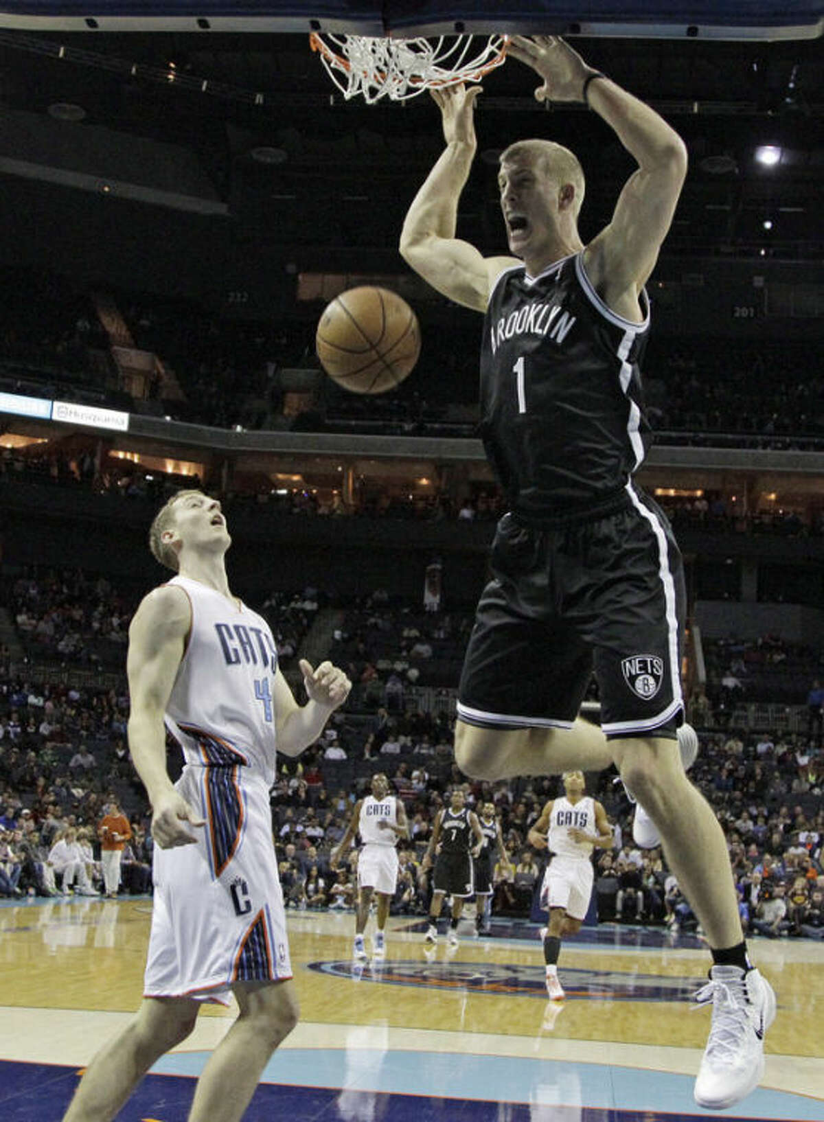 Brooklyn Nets' Mason Plumlee (1) dunks as Charlotte Bobcats' Cody Zeller stands by during the first half of an NBA basketball game in Charlotte, N.C., Wednesday, Nov. 20, 2013. (AP Photo/Chuck Burton)