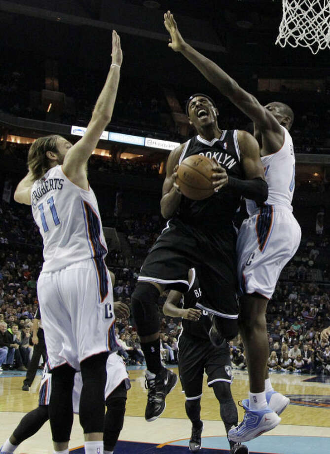Brooklyn Nets' Paul Pierce, center, drives between Charlotte Bobcats' Josh McRoberts, left, and Bismack Biyombo, right, during the first half of an NBA basketball game in Charlotte, N.C., Wednesday, Nov. 20, 2013. (AP Photo/Chuck Burton)