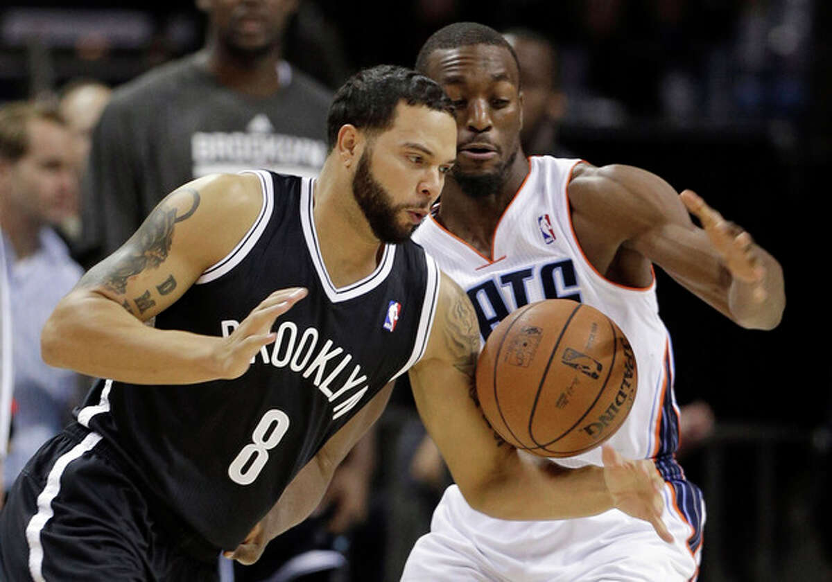 Brooklyn Nets' Deron Williams (8) loses the ball to Charlotte Bobcats' Kemba Walker during the first half of an NBA basketball game in Charlotte, N.C., Wednesday, Nov. 20, 2013. (AP Photo/Chuck Burton)
