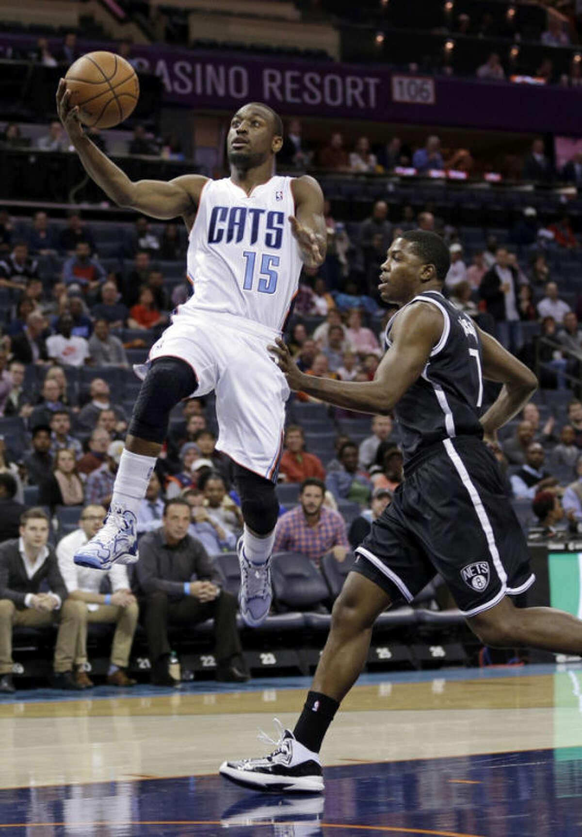 Charlotte Bobcats' Kemba Walker (15) drives past Brooklyn Nets' Joe Johnson during the first half of an NBA basketball game in Charlotte, N.C., Wednesday, Nov. 20, 2013. (AP Photo/Chuck Burton)