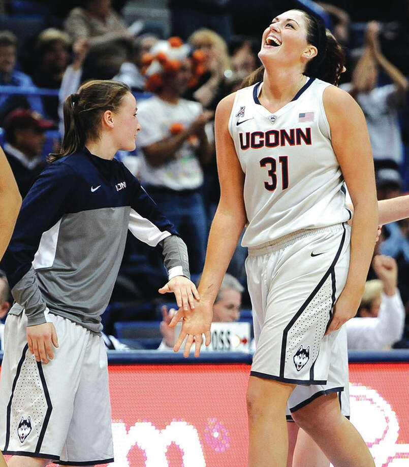 AP photoUConn's Stefanie Dolson, right, is all smiles as she leaves the court and is greeted by teammate Tierney Lawlor during a second-half time out in Wednesday night's game against Oregon at the XL Center. The 6-5 senior center became the second player in UConn women's hoop history to record a triple-double. Dolson collected 26 points, 14 rebounds and 11 assists in UConn's 114-68 victory. / FR125654 AP