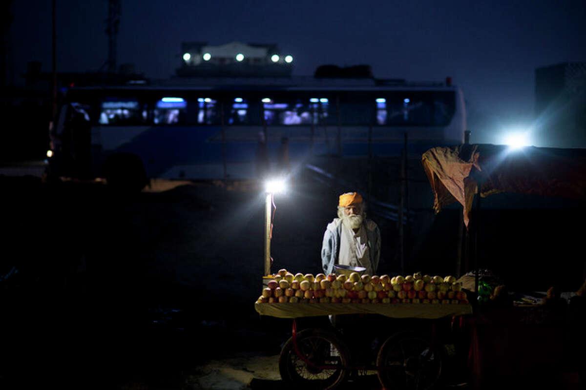 Pakistani vendor, Bakhtar Massi, 73, stands by his cart waiting for customers on a roadside in Rawalpindi, Pakistan, Wednesday, Nov. 20, 2013. (AP Photo/Muhammed Muheisen)