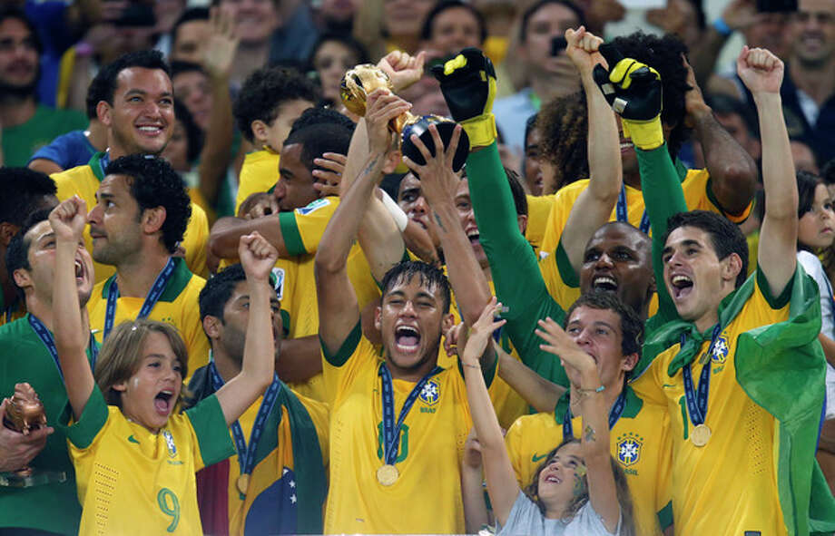 FILE - This Sunday, June 30, 2013 file photo shows Brazil's Neymar, center, as he lifts the trophy after winning the soccer Confederations Cup final between Brazil and Spain at the Maracana stadium in Rio de Janeiro, Brazil. (AP Photo/Victor Caivano, File) / AP