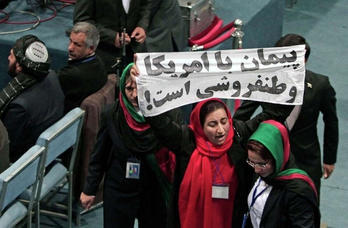 A member of the Afghan Loya Jirga holds a banner with Pashto that reads,