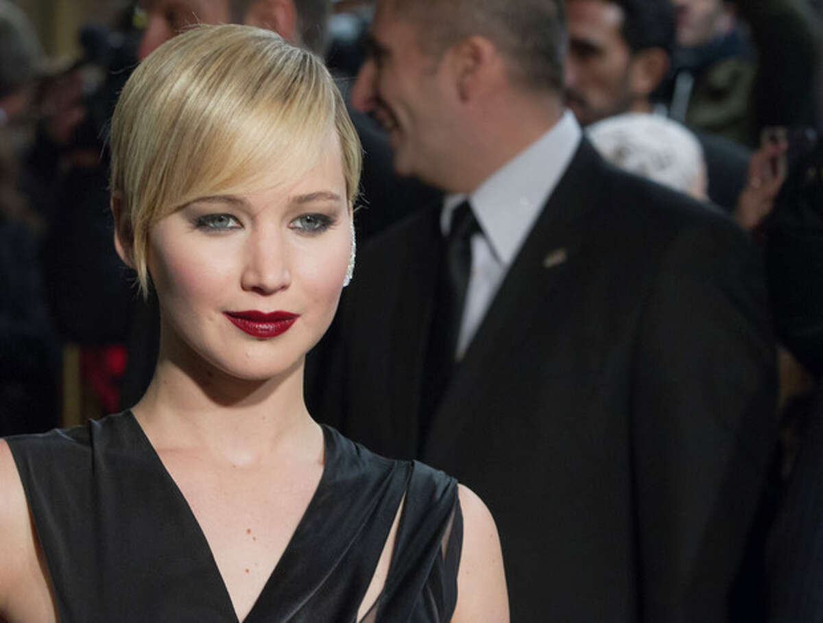 """This Friday, Nov. 15, 2013 shows US actress Jennifer Lawrence during the France premiere of the movie, """"The Hunger Games: Catching Fire,"""" at Rex Cinema in Paris, France. Lawrence returns Nov. 22, 2013, as Katniss Everdeen in the young-adult sci-fi sequel, following her best actress Academy Award for her work in ?""""Silver Linings Playbook."""" The 23-year-old Kentucky-bred Lawrence has gained an Oscar, spearheaded a colossal sci-fi film franchise and appeared on the cover of Vogue?'s 2013 September issue. (AP Photo/Jacques Brinon)"""