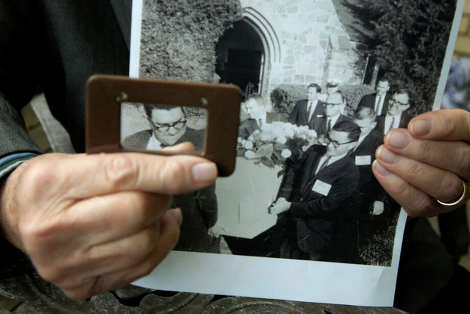 Mike Cochran poses holding a photo Friday, Nov. 15, 2013, at his home in Haltom City, Texas, using a magnifying glass to highlight his face along with other reporters serving as pallbearers. On a gloomy November afternoon, I helped carry the inexpensive wooden casket of Lee Harvey Oswald to a grave on a slight rise dotted with dying grass. (AP Photo/Tony Gutierrez) / AP