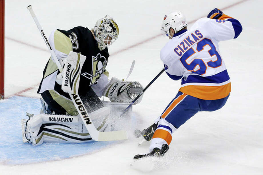 Pittsburgh Penguins goalie Jeff Zatkoff (37) stops a shot by New York Islanders' Casey Cizikas (53) in the first period of an NHL hockey game in Pittsburgh, Friday, Nov. 22, 2013. (AP Photo/Gene J. Puskar) / AP